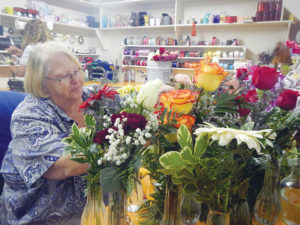Andee Erickson / Messenger photo Longtime owner of Farmer's Country Floral, Anita Farmer, makes a dozen bud vases on a June morning two months after Kristine Simmons bought the business.