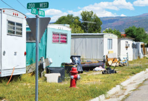 Refuse and belongings dot the strip behind a crowded row of mobile homes in Ephraim. The Ephraim City Council has decided the city can no longer let building, electrical, plumbing and other code violations at the park slide. - Robert Stevens / Messenger photo