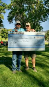 Buck Buford (left) and Kerry Carver hold up their $300 prize check after winning the cornhole tournament at the Sanpete County Fair last weekend.