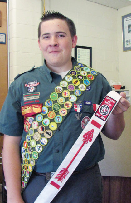 Dustin Zeeman is wearing his Scout bandalo sporting 142 merit badges, all the merit badges the Scouts offer. He is holding his Order of the Arrow sash signifying admission to the Scout honor society.