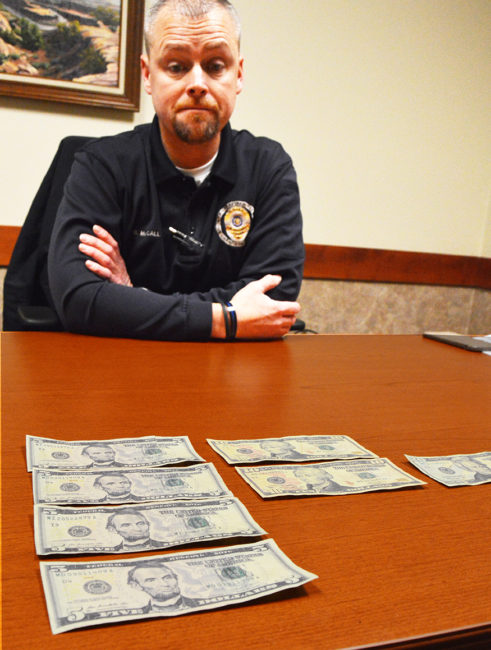 Gunnison Valley Police Interim Chief Brett McCall spreads out a selection of counterfeit currency that has begun circulating in Sanpete as far north as Fairview. McCall's department has made three arrests regarding the false bills so far and has more suspects under investigation. - Robert Stevens / Messenger photo