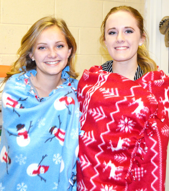 Madeynn Hill and Brinley Bown are wrapped in two of the many fleece blankets students made to donate to the Children's Justice Center, just in time for the holidays.