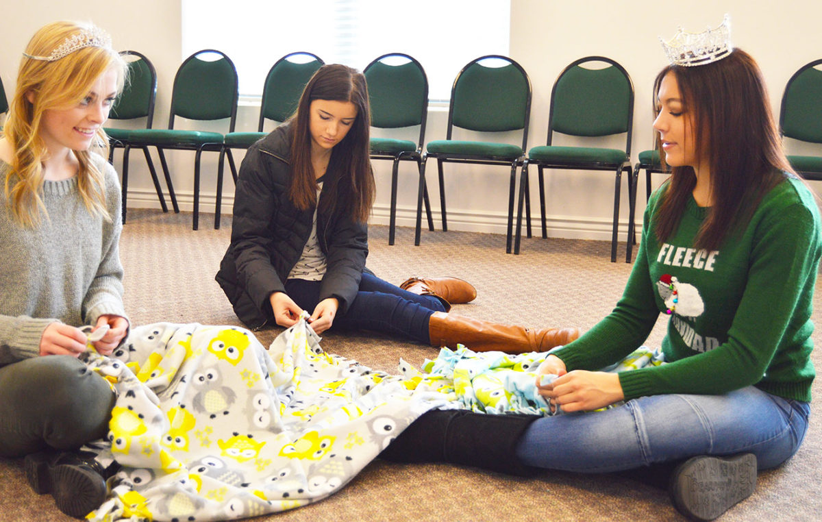 From left to right is Moroni City Royalty attendant Janey Christensen, Brooklyn Burgess and Moroni City Queen Kailee Burgess tying quilts to give to Primary Children's Hospital.