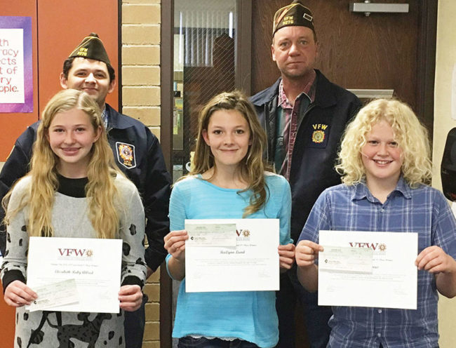 The local Veterans of Foreign Wars Post 9276 awarded cash prizes to three elementary students for winning a patriotic essay contest. From left to right on the front row is Elizabeth Allred who won first place and will compete at the district level, BreiLynn Lund won second place, and Kyle Morris won third place. Back row is VFW Scholarship Committee Chairman Jamie Rodriguez and Post Commander David Tucker.
