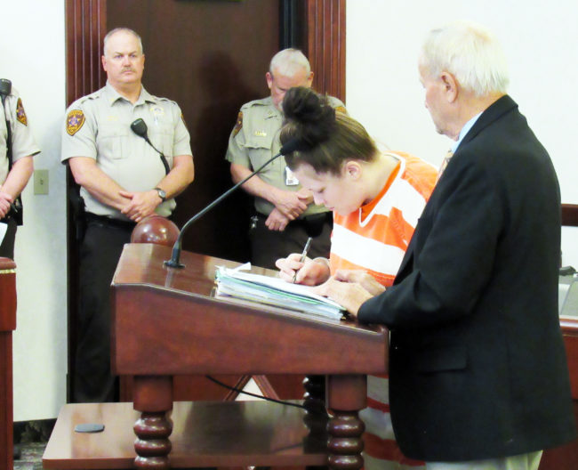 Angela Atwood signs her plea agreement in 6th District Court on Wednesday, March 8.