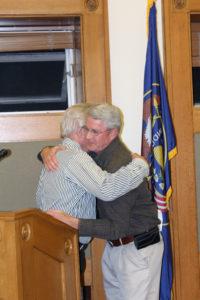 John Keeler gets a hug from John Eliason, local agent for Farm Bureau Insurance after Keeler receives the Sanpete County Farm Bureau Distinguished Service Award.