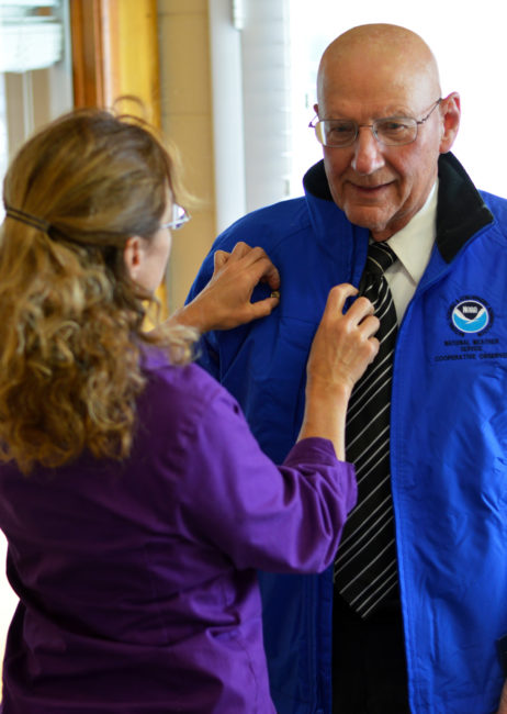Lisa Verzella, who coordinates volunteer weather observers in Utah for the National Weather Service, pins a 40-year service pin on Lee J. Anderson's jacket. Anderson received a national award plaque, a plaque for 40 years of service, the jacket and the pin during a presentation last Wednesday in the Sanpete Messenger office.