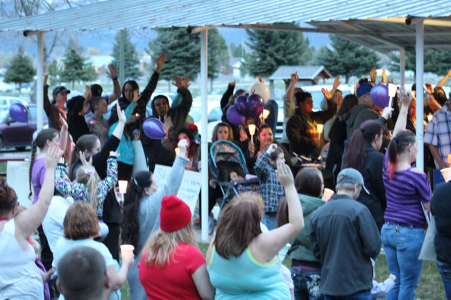 "People who had ever been made to laugh ""so hard you almost wet your pants"" by Kammy Edmunds raise their hands at a candlelight vigil in Edmunds' honor on Wednesday, April 5 at the Mt. Pleasant City Park. The vigil not only memorialized Edmunds, but promoted prevention and awareness of domestic violence, which is presumed to be a proximate cause of Edmunds' death on March 31."