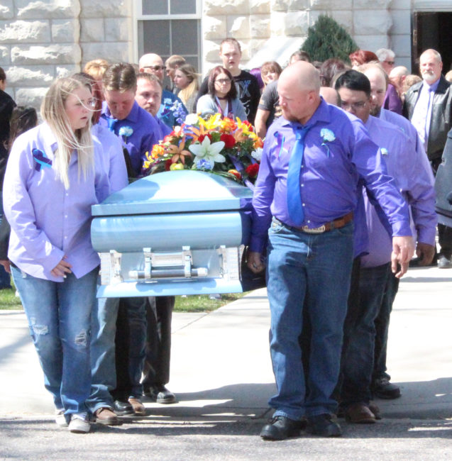 Pallbearers carry the casket containing the remains of Kammy Edmunds during funeral services on Saturday, April 8 at the Spring City LDS chapel. Many at the funeral, including pallbearers, wore purple—the color that represents domestic violence.