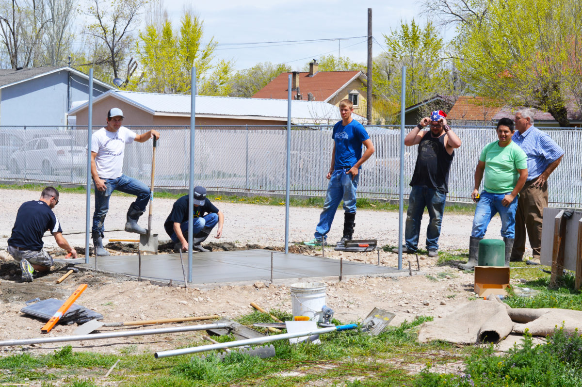 Students from Snow College's Building Layout and Concrete class, led by instructor Ivan Starr, install a concrete pad for a dumpster as part of the volunteer effort by Snow students and faculty to directly improve the DJ Trailer Park.