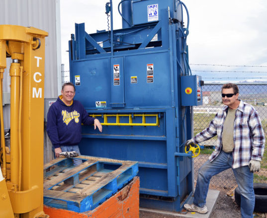 Todd Billings (left) and David Eicher, volunteers at the Sanpete Pantry, stand in front of the pantry's cardboard baler. The two men collect donated cardboard from across the county, bale it, and then sell it to generate revenue for the pantry. Pantry boatd member Guy Gee found the baler for $350, and transported it to Utah from Baltimore.