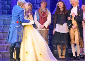 """Maurice played by Rory Anderson (left) kisses Belle played by Kylee Davis, as the dishes sing their approval inlast week's performance of """"Beauty and the Beast."""""""